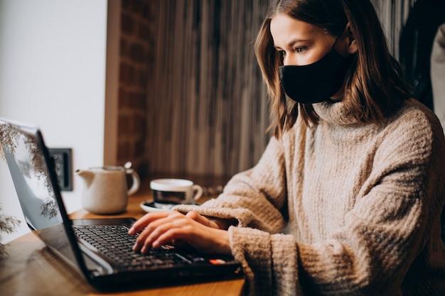 Jonge vrouw die aan laptop in een koffie werkt die masker draagt