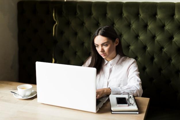 Jonge vrouw die aan laptop in koffie werkt