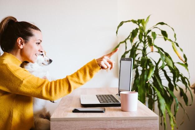 Jonge vrouw die aan laptop thuis werkt, leuke kleine hond daarnaast. thuis werken