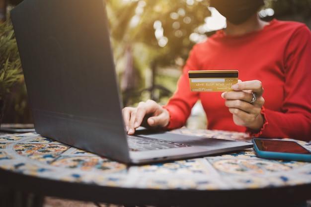Jonge vrouw die aan laptop werkt die creditcard toont