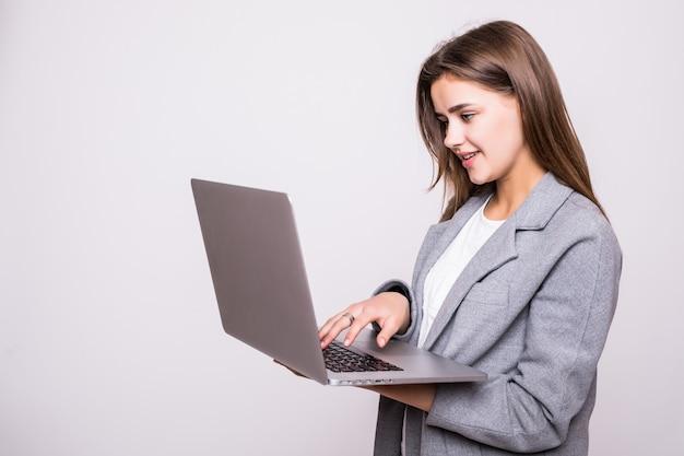 Jonge vrouw die aan laptop werkt die op witte achtergrond wordt geïsoleerd