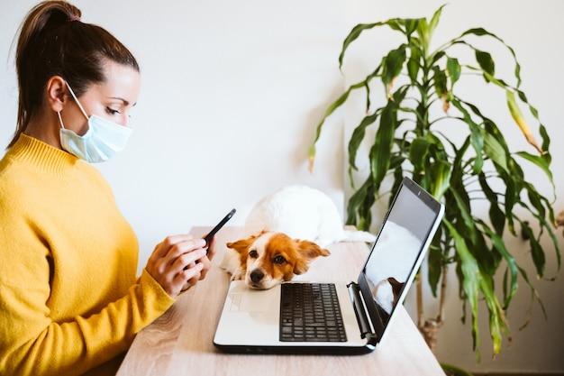 Jonge vrouw die aan laptop werkt die thuis, beschermend masker, leuke kleine hond draagt. werk vanuit huis, blijf veilig tijdens coronavirus covid-2019 concpt