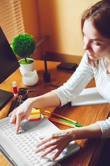 Jonge vrouw die aan laptop zittend op de werkplek werkt