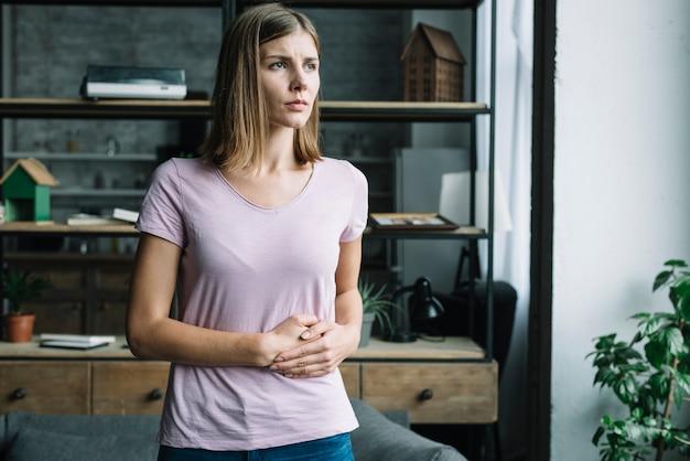 Jonge vrouw die aan maagpijn lijdt