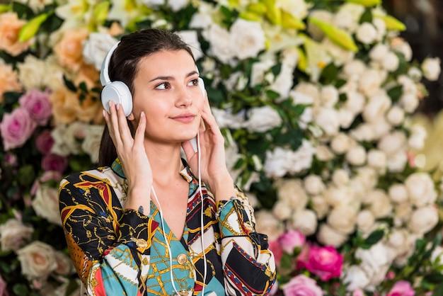 Jonge vrouw die aan muziek in groen huis luistert