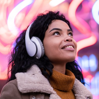 Jonge vrouw die aan muziek in hoofdtelefoons buiten luistert
