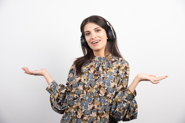 Jonge vrouw die aan muziek in hoofdtelefoons luistert.