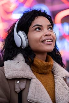 Jonge vrouw die aan muziek in hoofdtelefoons luistert