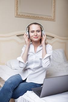Jonge vrouw die aan muziek luistert en laptop op het bed met behulp van