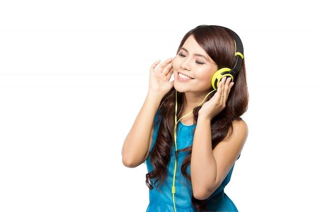 Jonge vrouw die aan muziek met geïsoleerde hoofdtelefoon luistert