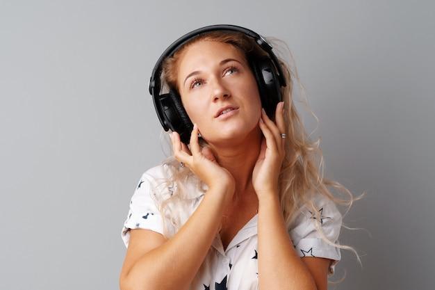 Jonge vrouw die aan muziek met haar hoofdtelefoons luistert