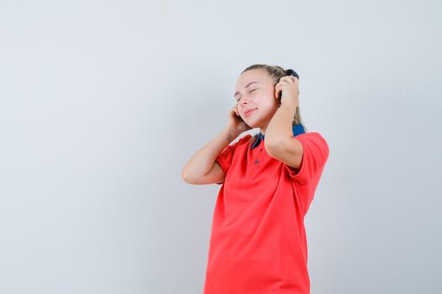 Jonge vrouw die aan muziek met hoofdtelefoons in t-shirt luistert en verrukt kijkt