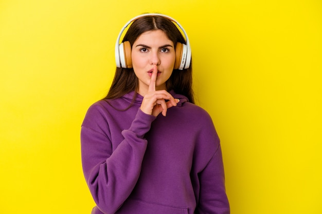 Jonge vrouw die aan muziek met hoofdtelefoons luistert die op roze muur wordt geïsoleerd die een geheim houdt of om stilte vraagt