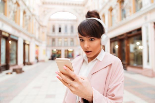 Jonge vrouw die aan muziek met hoofdtelefoons luistert