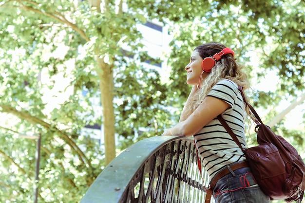 Jonge vrouw die aan muziek met hoofdtelefoons luistert.