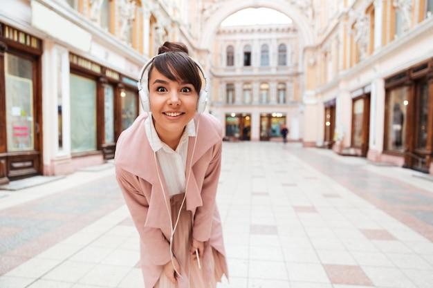 Jonge vrouw die aan muziek met hoofdtelefoons op een stadsstraat luistert