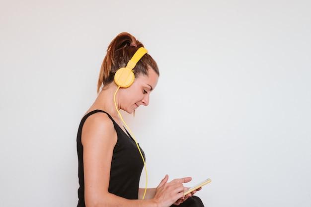 Jonge vrouw die aan muziek op gele mobiele telefoon en hoofdtelefoon luistert.