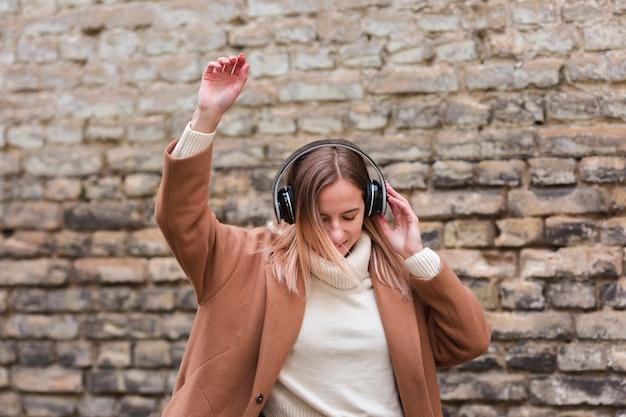 Jonge vrouw die aan muziek op hoofdtelefoons buiten luistert