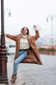 Jonge vrouw die aan muziek op hoofdtelefoons in de stad luistert