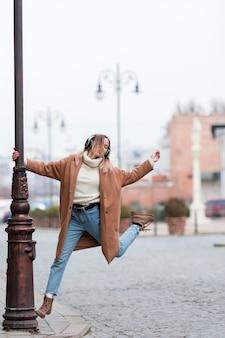 Jonge vrouw die aan muziek op hoofdtelefoons in de stad met exemplaarruimte luistert
