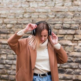 Jonge vrouw die aan muziek op hoofdtelefoons in openlucht luistert