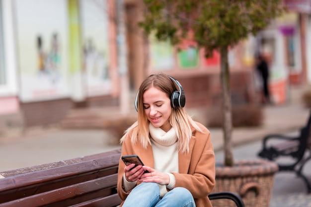 Jonge vrouw die aan muziek op hoofdtelefoons luistert