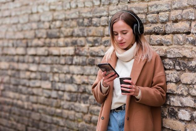 Jonge vrouw die aan muziek op hoofdtelefoons met exemplaarruimte luistert