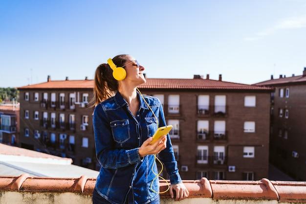 Jonge vrouw die aan muziek op mobiele telefoon en gele hoofdtelefoon luistert. plezier en levensstijl