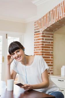 Jonge vrouw die aan muziek op smartphone luistert terwijl het hebben van koffie in keuken