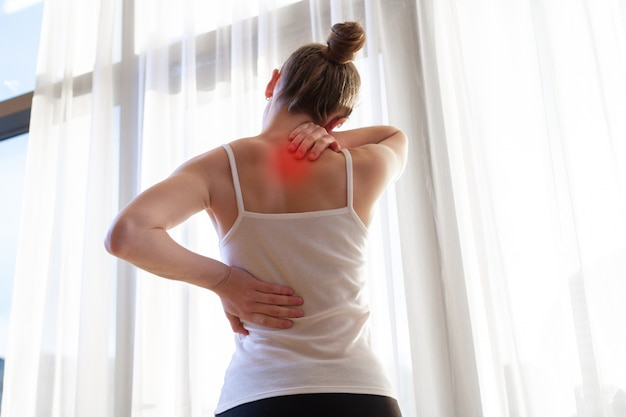 Jonge vrouw die aan nekpijn en rugpijn lijdt, die de spieren thuis uitrekt. rug- en nekpijn vrouw