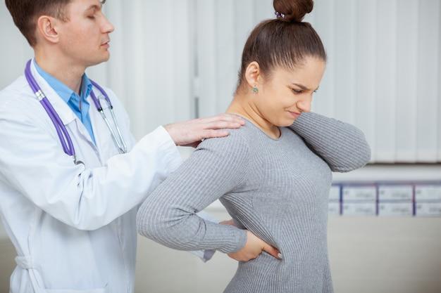 Jonge vrouw die aan rugpijn lijdt, die haar ruggengraat door een ervaren arts laat onderzoeken