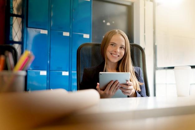 Jonge vrouw die aan tablet in modern startkantoor werkt