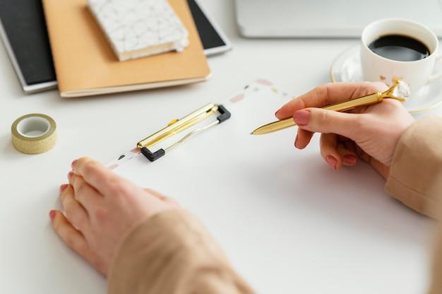 Jonge vrouw die aantekeningen op een klembord schrijft