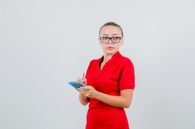 Jonge vrouw die aantekeningen op klembord in rood t-shirt, glazen en peinzend kijkt