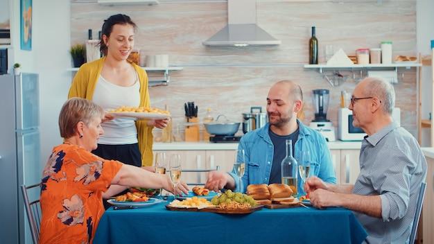 Jonge vrouw die aardappelen op tafel zet en een glas wijn rammelt met haar man. kaukasisch gezin geniet van de tijd thuis, in de keuken zittend aan tafel, samen etend en drinkend