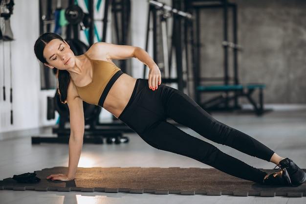 Jonge vrouw die abs training doet bij de gymnastiek