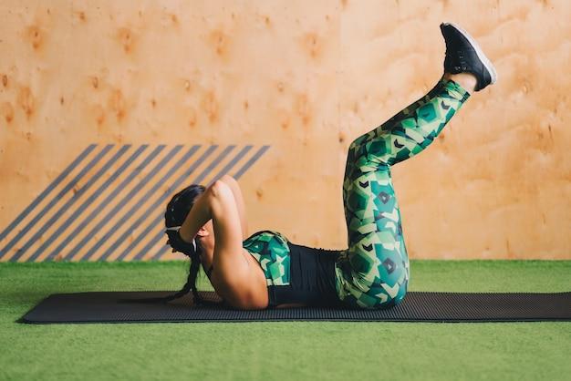 Jonge vrouw die abs training in een gymnastiek op een mat doet.