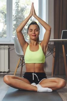 Jonge vrouw die ademhalingsoefening op yogamat thuis maken