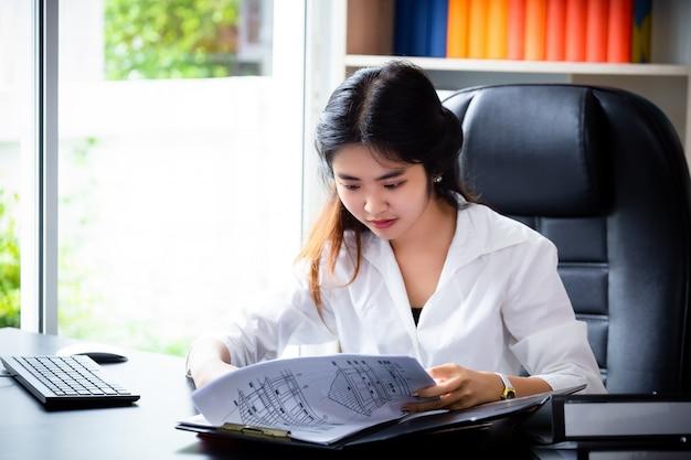 Jonge vrouw die administratie in omslag kijkt