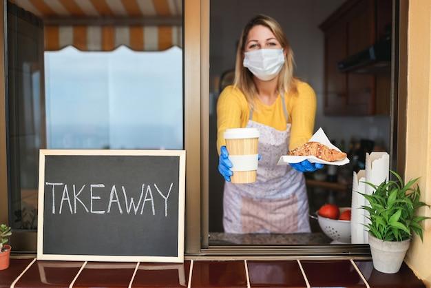 Jonge vrouw die afhaalontbijt en koffie in bakkerijwinkel voorbereidt terwijl zij veiligheidsmasker draagt - nadruk op voedsel
