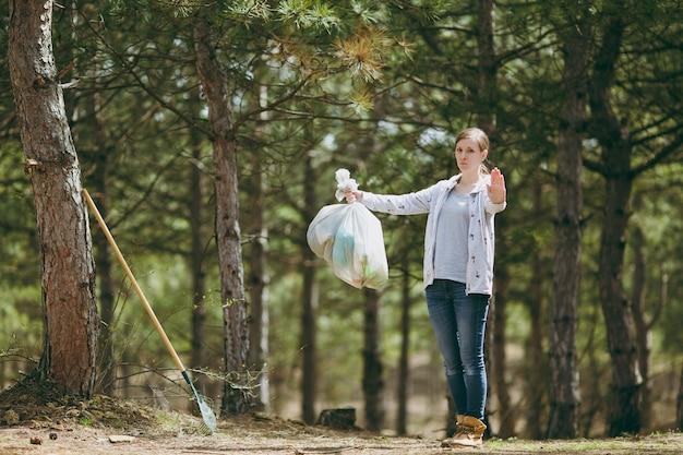 Jonge vrouw die afval schoonmaakt met vuilniszakken en stopgebaar met palm in park toont. probleem van milieuvervuiling