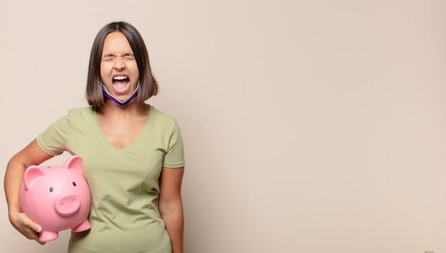 Jonge vrouw die agressief schreeuwt, er erg boos, gefrustreerd, verontwaardigd of geïrriteerd uitziet, nee schreeuwt
