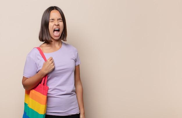Jonge vrouw die agressief schreeuwt, erg boos, gefrustreerd, verontwaardigd of geïrriteerd kijkt, nee schreeuwt
