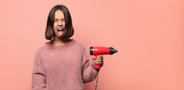 Jonge vrouw die agressief schreeuwt, erg boos, gefrustreerd, verontwaardigd of geïrriteerd kijkt