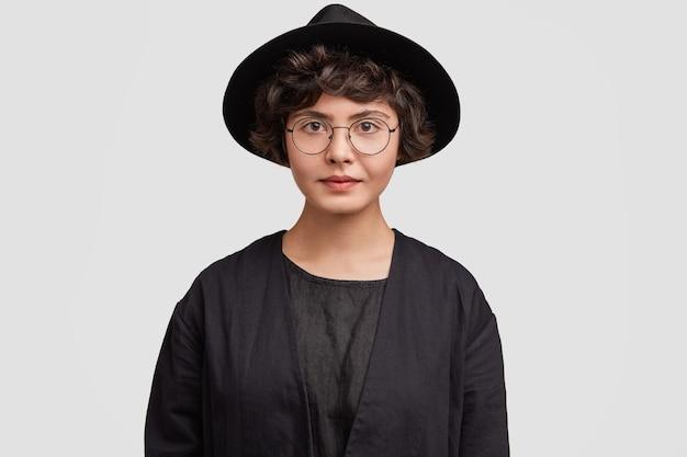 Jonge vrouw die alle zwarte kleren en ronde oogglazen draagt