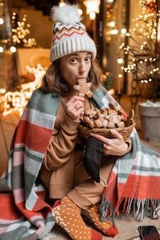 Jonge vrouw die alleen nieuwjaarsvakantie viert, zittend met zoete peperkoeken op een terras thuis. concept van quarantaine en zelfisolatie tijdens de epidemie op feestdagen