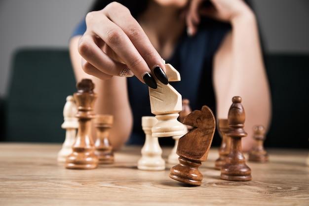 Jonge vrouw die alleen schaak speelt