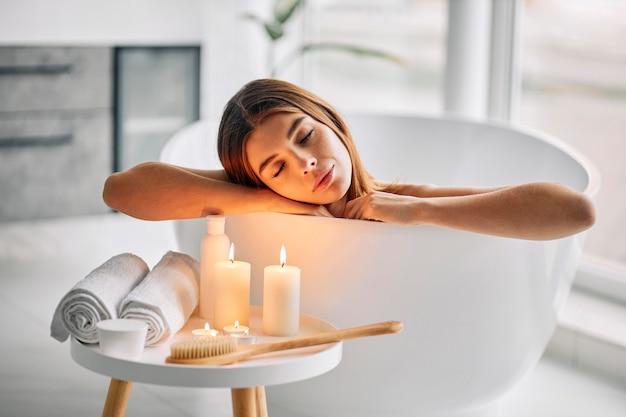 Jonge vrouw die alleen van een bad geniet