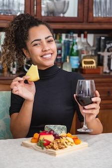 Jonge vrouw die alleen wijn drinkt en kaas eet in de woonkamer. vrouw die kaassnacks eet en wijn drinkt om te ontspannen na het werk.