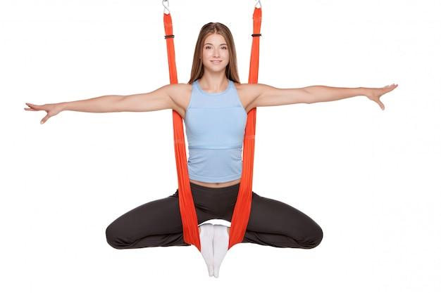 Jonge vrouw die anti-zwaartekracht luchtyoga doet